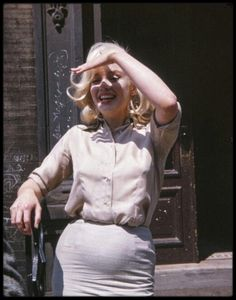 """1960 / Marilyn sous de la fan Frieda HULL, lors de sa sortie des essayages coiffures pour le film """"The misfits""""."""