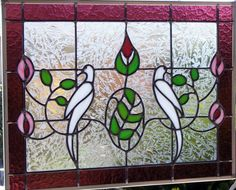 I designed and handcrafted this window using a design of white doves,pink flowers and green leaves with a beautiful accent border of purple wishmach glass.This window measures 22 1/8 inch long by 16 5/8 inches tall.  This stained glass window panel is made of leaded glass. It is not copper foil. The panel is sealed with a traditional putty formula. This makes the panel stronger and more durable than copper foil so that it can be displayed inside or outside.