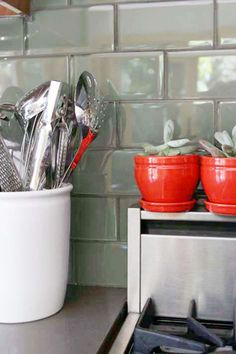 Beautiful kitchen- the complement of the tile and red potted succulent is so gorgeous!