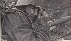 Italian soldier on the Eastern Front points to the spot where a bullet or ricochet hit his helmet.