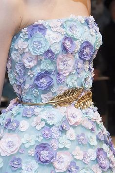 The delicate, pearlescent quality of the gown's flowers contrasted with the rich, glimmering golden belt.