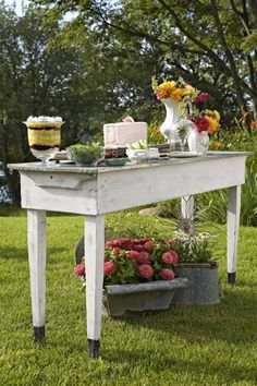 A thoughtful mix of textures lends the tabletop instant charm. Here, a pair of porcelain pitchers holds bouquets of garden-fresh flowers atop a galvanized-metal-top table. This buffet offers a build-your-own-salad of crisp lettuce leaves, candied walnuts, fresh raspberries, and vinaigrette in a mix of vintage bowls, along with a trifle, juicy watermelon, and an old-fashioned sandwich loaf made from chicken and tuna salads layered between bread and topped with pink-tinted cream cheese.