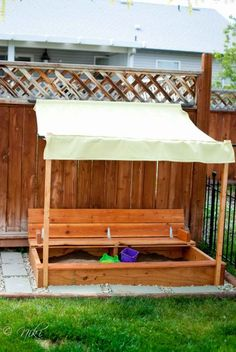 Sandbox with cover that folds up to seats!  This one modified with a sunshade - love it!
