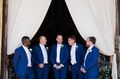 groom and groomsmen in blue suits chatting at Titchfield barn by jenny owens photography