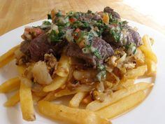 Chorrillana is a Chilean pub food french fry dish, covered by a sliced steak, an egg, and S.mmm