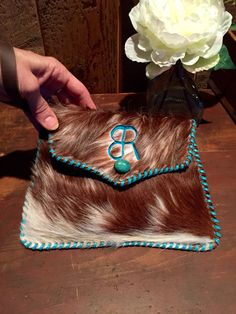 A cowhide Wristlet with the customers brand in turquoise suede and stitched in turquoise leather lace. From gowestdesigns.us