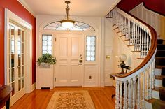 Foyer with curved staircase and entryway to living room with French doors.