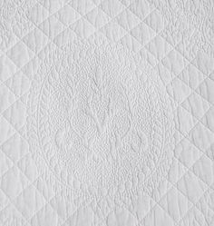 Close image of stitching in pure white quilted bedding