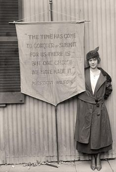 """Pauline Floyd, US Suffragette. Her audacious banner quotes President Wilson's own words back at him: """"The time has come to conquer or submit. For us there is but one choise. We have made it.""""  (Poor man thought he was only talking about the Great War.)"""