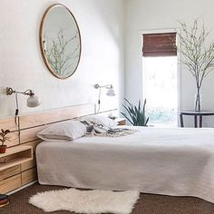 Beautiful bright sleeping room with a round mirror above the bed. Light colors, some plants wooden details create an calming effect. Perfect for sweet dreams! Head to our blog to find more inspiration!