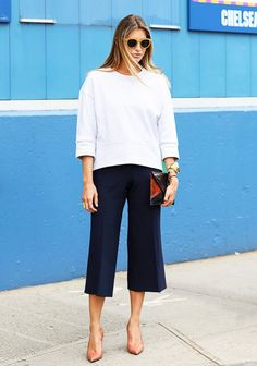 culottes with an oversized sweater accessorized with gold bangles and an envelope clutch