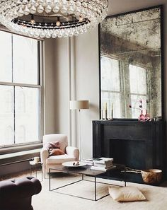 Sophisticated minimalist living room... Love the antiqued mirror and crystal drop chandelier