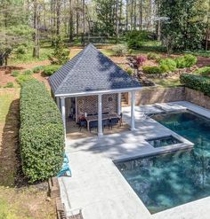 Little pool house with brick walls & covered seating area. In ground pool & concrete patio. Hot tub. Red brick retaining walls.