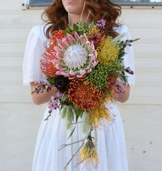 Fleurie Florals of Reedley, California, Cascading bridal bouquet of pincushion proteas, berzillia berries - like a fireworks display in your hands!