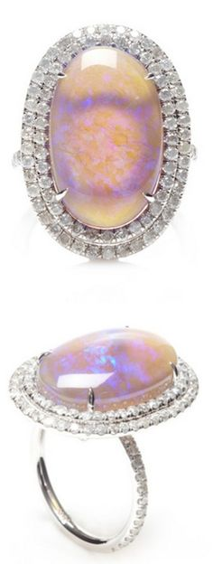 This one of a kind Nina Runsdorf ring features violet lightning ridge opal cabochon surrounded by two rows of diamond pave, fashioned in 18k white gold.