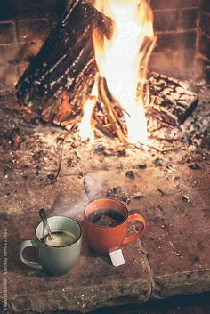 Hot cups of coffee and tea by a fireplace