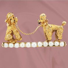 A jolly pair of poodles in 14K yellow gold on a pearl bar pin, a lighthearted 50s design. This pin measures 1 1/2 X 2