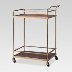 Get ready for any big gathering or enjoy a quiet night in with loved ones with this Wood & Brass Bar Cart from Threshold™. Perfect for adding to your living room or dining room, you'll love serving guests or yourself a delicious drink with the convenience of this bar cart. Whether you create an at-home coffee/tea station or a setup to enjoy homemade cocktails, this bar cart makes doing so a breeze — two levels let you store bottles, glassware, decorative pieces...