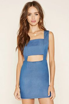 Crafted from denim, this sleeveless overall dress by Nightwalker™ features a mini length, a square neckline, a waist cutout, adjustable straps, a ladder-cutout V-back with two button accents, and a concealed side zipper. #thelatest