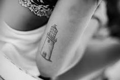 A Small Lighthouse Tattoo On Arm