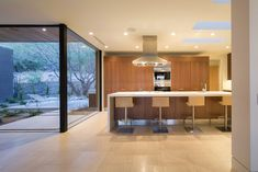 Tagged: Kitchen, Limestone Floor, Quartzite Counter, Recessed Lighting, Wood Cabinet, Refrigerator, Microwave, Cooktops, Range Hood, Wall Oven, and Undermount Sink.  Photo 18 of 32 in Rammed Earth Modern by Brent Kendle / Kendle Design Collaborative