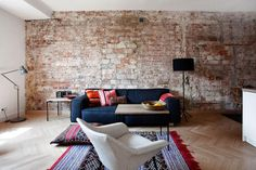 I love that brick unfinished wall look, the colour of the sofa which is emphasised by the mix of pillows and rug - Living Corriere