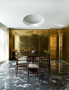 bold brass walls + marble flooring - juxtaposed perfectly with a minimalist dining room table