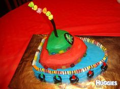 Tug-boat 3 tiered chocolate cake. Decorated with blue, red and green icing. Accessory lollies include: licorice, licorice allsorts, wine-gums, jelly-beans, a pineapple lump for the motor, and coloured popcorn for the smoke!