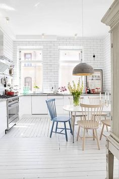 Subway tile, white painted wood floors, pop of color chair, dining pendant, large frame, stainless steel.