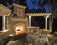Outdoor fireplace with pergolas and bench seating flanking either side. Large mantel. Could include grill outdoor kitchen too. Table set for dinner. From Alder Group, Pool Landscape Co.