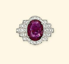 A RUBY AND DIAMOND RING. The oval-shaped ruby weighing 3.03 carats mounted within a millegrain-set brilliant-cut diamond surround of geometric design to the plain hoop. Undated but assumed to be Art Deco or Art Deco style.