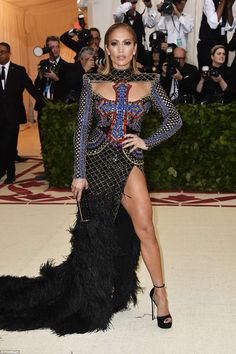 Perfection: Jennifer Lopez commanded attention in her Balmain gown, which featured a large cross on her torso with a feathered train