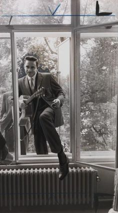 Johnny Cash climbing through a window, guitar in hand, taken in September 1959 by A Tanner.