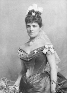Jennie Churchill's dress features the substantial upswept bustle of the mid and late 1880s as well as the sleeveless bodice fashionable at the time. The three feather headdress shows she is dressed for court. Her bodice and bustle appear to to be made of velvet, while her skirt appears to be covered by very sheer material.