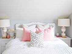 In designer Jillian Harris's home, a lovely little headboard defines the space below the sloped ceiling, while matching nightstands with stately lamps create height.   Photographer: Janis Nicolay