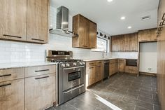 """""""After"""" photos of 10th flip - It's Great to Be Home.  Kitchen with stained maple cabinets, subway tile with gray grout, carrera marble counter, cedar + moss sconces, gray porcelain tile floor, black hardware, rustic modern"""