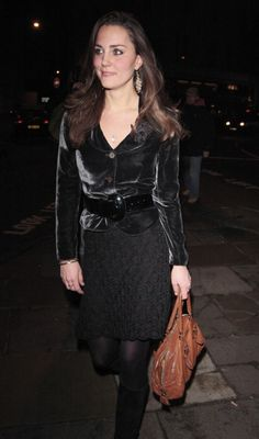 Kate, dressed in a black skirt, velvet belted blazer, black tights, and black heels, paired with a tan bag making a fresh statement in between all of the black.