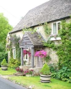 a quaint English cottage, made even lovelier by the climbing ivy and hanging baskets of colorful flowers.
