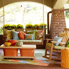 Colorful Fall Porch  Take a color scheme through the season with pretty, inexpensive fall accents. Outdoor pillows add pick-me-up to a porch swing while a small throw rug keeps the palette going. Make a simple table by sandwiching two colorful tubs between slabs of wood. We added wheels to the base board to make it mobile.