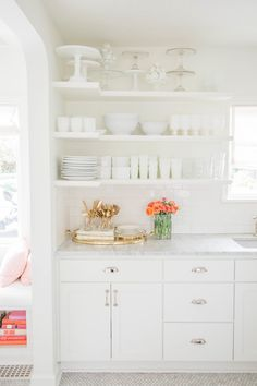 White kitchen with orange, peach and gold pops of color: Photography : Emma Rose Company Read More on SMP: http://www.stylemepretty.com/living/2016/08/31/the-perfect-color-combo-for-an-eternally-bright-and-happy-home/