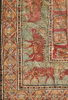 Detailed Image of The Pazyryk - THE OLDEST CARPET IN THE WORLD -  It is housed at St. Petersburg's Hermitage Museum.  Its decoration is rich and varied: the central field is occupied by 24 cross-shaped figures, each of which consists of four stylized lotus buds.  This composition is framed by a border of griffins, followed by a border of twenty-four fallow deer.The widest border contains representations of workhorses and men.