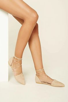 A pair of faux suede flats featuring a pointed toe, cutout sides, and a strappy lace-up front that ties around the ankle.