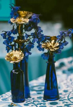 Beautiful bold blue centerpies mix in vintage gold candleholders of different sizes to complete the look