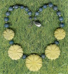 Pale yellow, soft blue, and a shimmer of delicate green is just what the season calls for. Nicely carved, substantial flowers will make everyone smile at you. The graduated, yellow Aventurine beads measure 15/8, 13/8 and 1. The blue Aventurine round beads are 12mm, 10mm and 8mm, and the rondelles are 10x6mm. They are all separated by 3 - 4mm nuggets of luminous Freshwater Pearls. The designer leaf clasp and other components are Sterling Silver and the length is 18 inches. Truly, a u...