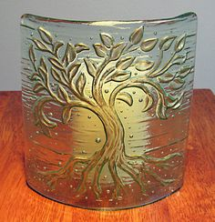 This pale green curved glass piece will enhance a candle in any room. The embossed tree image is kiln formed into the back of the glass. The leaves, trunk and branches are hand painted with a golden metallic finish which shimmers when lit from the front, and is opaque when lit from the back. The piece is free standing with an elliptical form which makes the tree image visible from multiple angles. This work has been kiln fired twice: once to create the tree embossing and again, after…