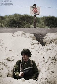An American soldier hidden in a trench watches the beach, Above him, the German placard reads that the area is mined, Utah beach, Normandy, France, June 1944