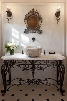 A Spanish romantic-style bathroom with a vanity made of an antique stone basin and custom wrought iron details.