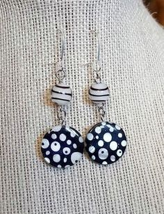 "Black and White Circles Dots Mother of Pearl Lampwork Glass Dangle Drop Earrings $12.00 These+earrings+can+go+with+just+about+anything.++They+are+made+with+black+and+white+mother+of+pearl+shell+coins+and+round+black+and+white+lampwork+glass+beads+attached+to+silver+plated+kidney+wires.++They+measure+2.4""+from+the+top+of+the+wire+to+the+bottom+of+the+coin+bead.++"