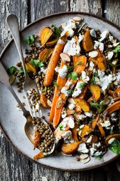 In this Roasted Beet & Carrot Lentil Salad, warm lentils topped with roasted vegetables get a boost from herbed yogurt sauce, feta, and crunchy almonds.