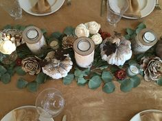 Fall/Thanksgiving tablescape using white ceramic pumpkins, eucalyptus branches and candles.